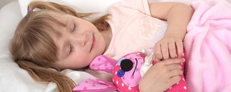 Plüssállattal alvó kislány